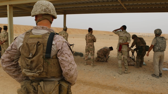 U.S. Marine Cpl. Kyle Bacon, left, a team leader with Weapons Company, 1st Battalion, 7th Marine Regiment, provides security for Royal Danish Army shooting instructors during a live-fire range at Al Asad Air Base, Iraq, Oct. 26. The training was conducted as a part of the building partner capacity mission utilizing both U.S. and Danish forces to teach the Iraqi security forces proper weapons handling and other various combat skill sets.