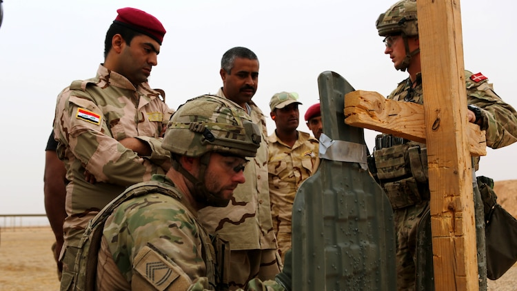Royal Danish Army Sgt. 1st Class Martin, left, a primary shooting instructor, marks shot groups during a live-fire range at Al Asad Air Base, Iraq, Oct. 26, 2015. The training was a part of the Combined Joint Task Force – Operation Inherent Resolve building partner capacity mission to teach the Iraqi soldiers proper marksmanship techniques to improve their effectiveness on the battlefield against the Islamic State of Iraq and the Levant.