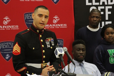 Sergeant Efarin Broutan, a canvassing recruiter for Marine Corps Recruiting Sub-Station Shreveport, speaks before presenting C.J. Morgan-Walker, a cornerback for Parkway High School in Bossier City, La., with a Semper Fidelis All-American Bowl game jersey on Oct. 23, 2015. The student athletes selected for the Semper Fidelis All-American Bowl are committed to their communities and exhibit leadership both on and off the field.