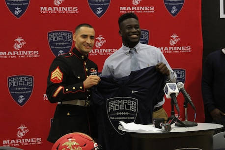 Sergeant Efarin Broutan, a canvassing recruiter for Marine Corps Recruiting Sub-Station Shreveport, presents C.J. Morgan-Walker, a cornerback for Parkway High School in Bossier City, La., with a Semper Fidelis All-American Bowl game jersey on Oct. 23, 2015. The student athletes selected for the Semper Fidelis All-American Bowl are committed to their communities and exhibit leadership both on and off the field.
