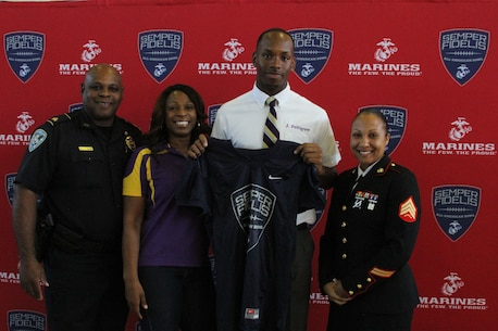 Sergeant Felicia Tanksley, a canvassing recruiter with Recruiting Sub-Station New Orleans, poses for a photo with Jamal Pettigrew and his parents during his jersey presentation held at Saint Augustine High School on Oct. 12, 2015. Pettigrew will be participating in the 2016 Semper Fidelis All-American bowl held in California on Jan. 3, 2016. For more information about the Semper Fi Bowl, visit www.semperfidelisfootball.com