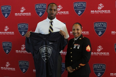 Sergeant Felicia Tanksley, a canvassing recruiter with Recruiting Sub-Station New Orleans, presents a Semper Fidelis All-American Bowl jersey to Jamal Pettigrew, a tight end for Saint Augustine High School on Oct. 12, 2015. The jersey presentation represents Pettigrew's acceptance to play in 2016 Semper Fidelis All-American bowl on Jan. 3, 2016.