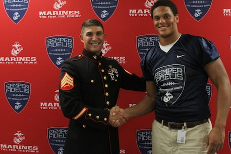 Sergeant Wesley Martins, a canvassing recruiter with Recruiting Sub-Station Baton Rouge North, poses for a photo with Caleb Roddy during his jersey presentation held at Saint Augustine High School on Oct. 12, 2015. Roddy is a defensive end for Denham Springs High School and will be participating in the 2016 Semper Fidelis All-American bowl held in California on Jan. 3, 2016. For more information about the Semper Fi Bowl, visit www.semperfidelisfootball.com