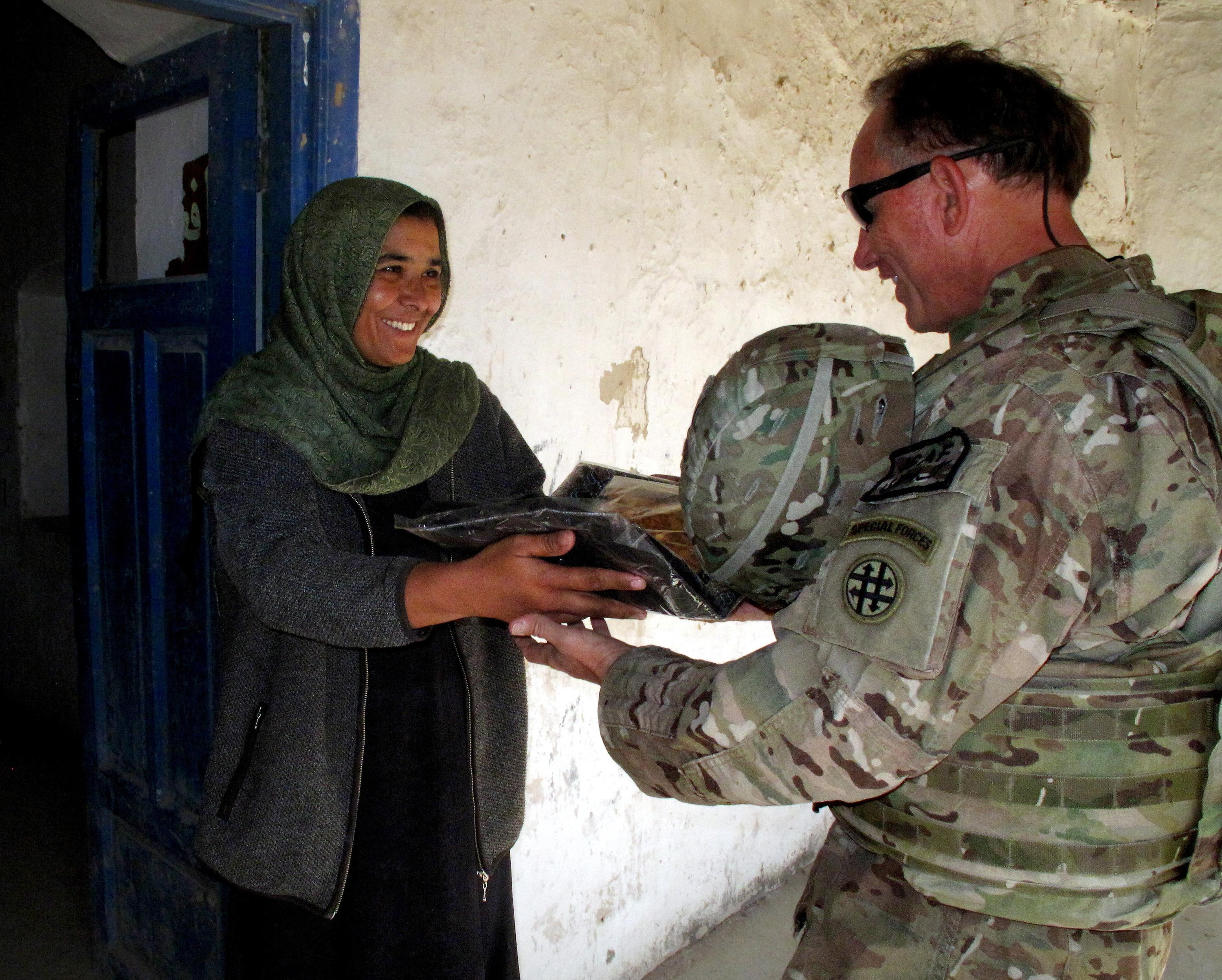 Army Lt  Col  Joel Jeffers receives gifts from Fatima, a