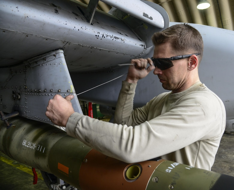 Staff Sgt. Christopher Uecker, 25th Aircraft Maintenance Unit weapons load crew team chief, tightens arming wire on an A-10 Thunderbolt II during the Vigilant Ace 16 exercise on Osan Air Base, Republic of Korea, Nov. 1, 2015. The arming wire holds the guided bomb unit in place until proper aerial release. (U.S. Air Force photo/Senior Airman Kristin High)