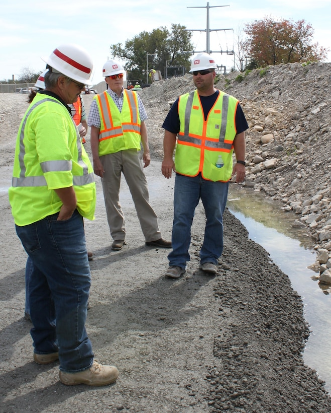 Geotechnical engineer, Eric Hackbarth (right), explains the benefits of using roller-compacted concrete for the Lockport forebay wall to safety specialist, Jim Trail (left), and cost engineering specialist Chuck Van Laarhoven (center).