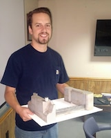 Greg Turko, civil engineer with the Pittsburg District, stands with their new 3D Emsworth Lock model that will be used for training new employees on the process of bulkhead installation.