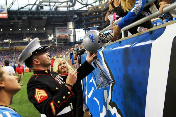 U.S. Marine Sgt. Benjamin J. Annarino signs a fan's helmet during a Detroit Lions football game at Ford Field in Detroit, Oct. 20, 2015. Annarino was honored as the game's Hometown Hero during a break in play in the third quarter. Annarino is a canvassing recruiter for Recruiting Station Detroit and a Livonia, Mich., native. U.S. Marine Corps photo by Sgt. J. R. Heins
