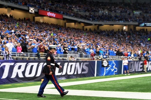 U.S. Marine Sgt. Benjamin J. Annarino walks onto the field as more than 60,000 fans cheer during a Detroit Lions football game at Ford Field in Detroit, Oct. 20, 2015. Annarino was honored as the game's hometown hero during a break in play in the third quarter. Annarino is a canvassing recruiter for Recruiting Station Detroit and a Livonia, Michigan, native. U.S. Marine Corps photo by Sgt. J. R. Heins