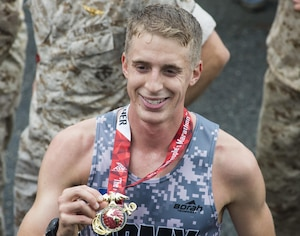 """Overall winner of the 40th Marine Corps Marathon, 22 year old U.S. Army Lt. Trevor Lafontaine, from Cornwall, N.Y., smiles and holds up his medal after completing his first marathon at 2:24:25 in Arlington, Va., Oct. 25, 2015. Also known as """"The People's Marathon,"""" the 26.2 mile race drew roughly 30,000 participants to promote physical fitness, generate goodwill in the community, and showcase the organizational skills of the Marine Corps. (U.S. Marine Corps photo by Staff Sgt. Sarah R. Hickory/Released)"""
