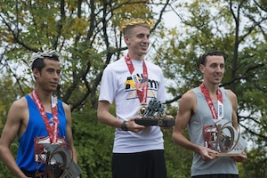"The top 3 finishers of the 40th Marine Corps Marathon (MCM), 1st place winner U.S. Army Lt. Trevor Lafontaine (center), from Cornwall, N.Y., 2nd place winner Oscar Mateo (left), of Mexico, and 3rd place winner Brian Flynn (right) of Rockingham, Va., pose for a photo after being crowned the winners of the 40th MCM at the award ceremony in Arlington, Va., Oct. 25, 2015. Also known as ""The People's Marathon,"" the 26.2 mile race drew roughly 30,000 participants to promote physical fitness, generate goodwill in the community, and showcase the organizational skills of the Marine Corps. (U.S. Marine Corps photo by Staff Sgt. Sarah R. Hickory/Released)"