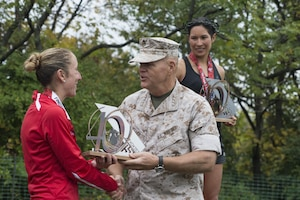 "U.S. Marine Corps Capt. Christine Taranto of Monterey, Calif., receives a trophy from the 37th Commandant of the Marine Corps, General Robert B. Neller, for 2nd place female finisher of the 40th Marine Corps Marathon at the awards ceremony in Arlington, Va., Oct. 25, 2015. Also known as ""The People's Marathon,"" the 26.2 mile race drew roughly 30,000 participants to promote physical fitness, generate goodwill in the community, and showcase the organizational skills of the Marine Corps. (U.S. Marine Corps photo by Staff Sgt. Sarah R. Hickory/Released)"