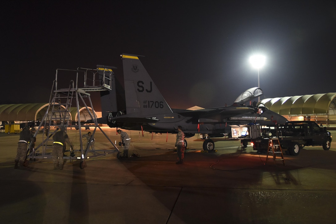 Airmen assigned to the 16th Electronic Warfare Squadron, Eglin Air Force Base, Florida, move a stand into position behind an F-15E Strike Eagle during Combat Shield, Oct. 20, 2015, at Seymour Johnson Air Force Base, North Carolina. Every year, members of the squadron evaluate the EW systems of all functional combat airframes within Air Combat Command in accordance with the Combat Shield program. (U.S. Air Force photo/Senior Airman Aaron J. Jenne)