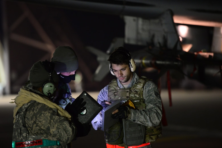 Senior Airmen Jonathon Simmons, 25th Aircraft Maintenance Unit load master, reviews system operational guidelineswith his crew during the first night of Vigilant Ace 16 at Osan Air Base, Republic of Korea, Nov. 2, 2015. Vigilant Ace is a peninusla wide operational readiness exercise geared toward strengthing the interoperability of the ROK/U.S.  alliance. 
