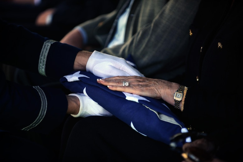 "Staff Sgt. Richard Bates, 47th Flying Training Wing Base Honor Guard NCO in charge presents the flag to retired Maj. Gen. Lewis's wife in Eagle Pass, Texas, on Oct. 28, 2015. Upon presentation of the flag, the presenter says, ""On behalf of the President of the United States, and a grateful Nation, please accept this flag as a symbol of our appreciation for your loved one's honorable and faithful service."" (U.S. Air Force photo by Tech. Sgt. Steven R. Doty)(Released)"