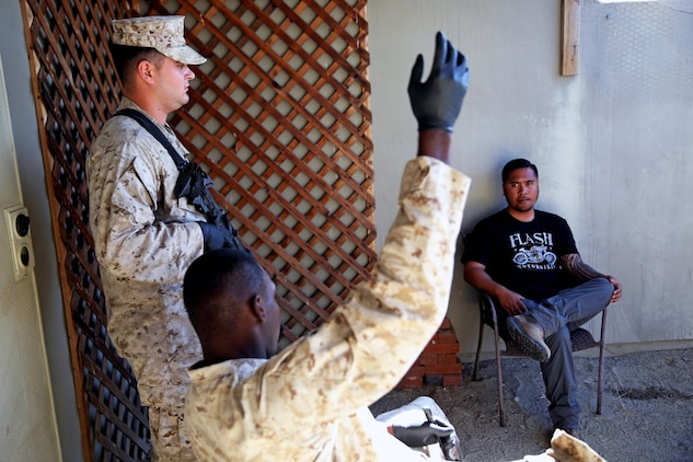 Marines with Headquarters and Service Company, 1st Battalion, 5th Marine Regiment, 1st Marine Division, speak with a role-playing suspect while searching his house during searchers and site exploitation training aboard Marine Corps Base Camp Pendleton, Calif., Oct. 29, 2015. Instructors with the Marines Corps Engineer Society taught the Marines the skills they need to locate and collect evidence on munitions or against suspected individuals in a realistic training environment.