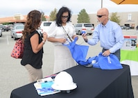 A representative (right) from Pacific Gas and Electric passes out promotional items Oct. 28 at the finale of Edwards AFB's Energy Action Month campaign. PG&E was joined by Southern California Edison, the 412th Civil Engineering Group and the Exchange during the event.(U.S. Air Force photo by Kenji Thuloweit)
