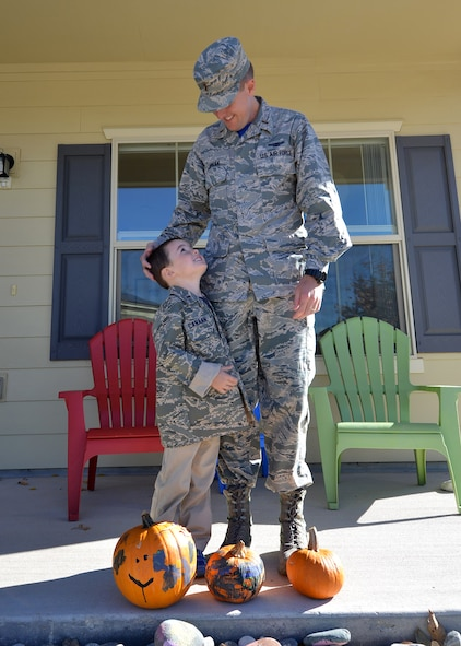 """Andrew Canaan looks up at his father, 2nd Lt. John Canaan, 1st Space Operations Squadron mission planning officer, Oct. 23, 2015, outside of their home at Schriever Air Force Base, Colorado. Andrew says when he grows up he wants to be a """"marching man"""" and work on satellites just like his father. (U.S. Air Force photo/Staff Sgt. Debbie Lockhart)"""