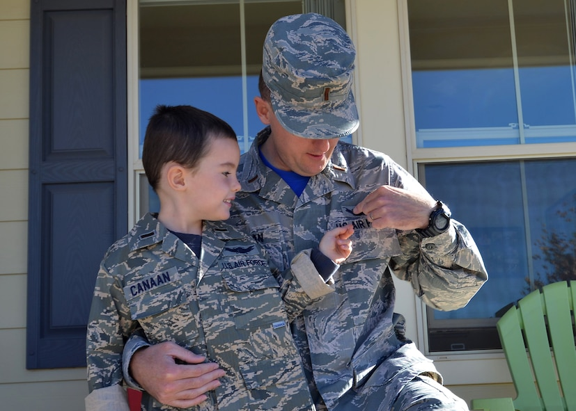 Second Lt. John Canaan, 1st Space Operations Squadron mission planning officer, shows his son, Andrew, his space badge Oct. 23, 2015, outside of their house at Schriever Air Force Base, Colorado. Since his father joined the U.S. Air Force, Andrew has developed a love of the military and space. (U.S. Air Force photo/Staff Sgt. Debbie Lockhart)