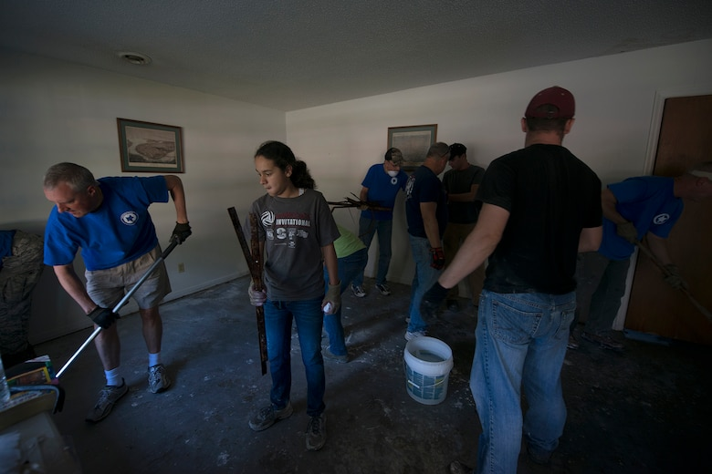 U.S. Airmen and family members from the 169th Fighter Wing, South Carolina Air National Guard, volunteer to provide assistance to residents in a Columbia neighborhood with the removal of household debris, which included the home of a former retired member of their unit, Oct. 8, 2015. The South Carolina National Guard has been activated to support state and county emergency management agencies and local first responders as historic flooding impacts counties statewide. Currently, more than 2,900 South Carolina National Guard members have been activated in response to the floods. (U.S. Air National Guard photo by Tech. Sgt. Jorge Intriago/Released)