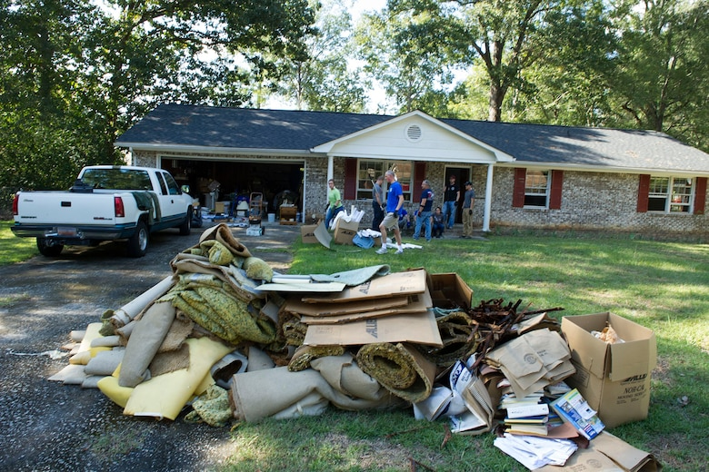 U.S. Airmen and family members from the 169th Fighter Wing, South Carolina Air National Guard, volunteer to provide assistance to residents in a Columbia neighborhood with the removal of household debris Oct. 8, 2015. The South Carolina National Guard has been activated to support state and county emergency management agencies and local first responders as historic flooding impacts counties statewide. Currently, more than 2,900 South Carolina National Guard members have been activated in response to the floods. (U.S. Air National Guard photo by Tech. Sgt. Jorge Intriago/Released)