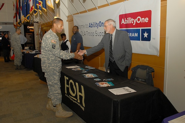 Army Brig. Gen. Charles R. Hamilton, commander of DLA Troop Support greets a vendor from the Federal Occupational Health organization at the AbilityOne Day expo Oct. 28 in Philadelphia. The event was held to increase awareness of the outstanding contributions people with disabilities have made to our nation and to highlight the products and services provided to our warfighters.