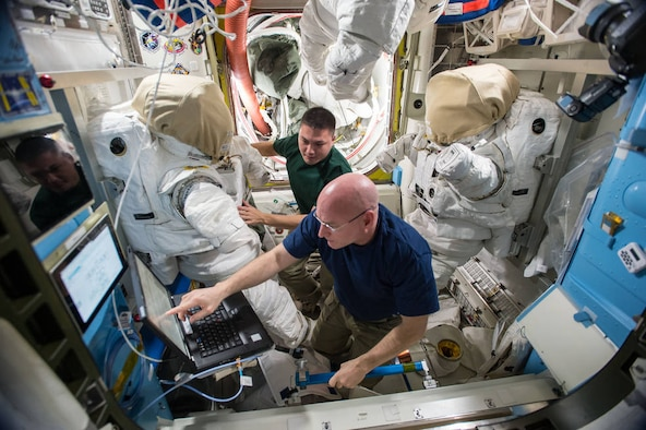 Astronauts Scott Kelly, front, and Kjell Lindgren, a 1995 Air Force Academy graduate, prepare their extravehicular mobility unit spacesuits and tools in the Quest airlock of the International Space Station. Kelly and Lindgren will use the spacesuits for a spacewalk outside the station Nov. 6, 2015. (NASA courtesy photo)