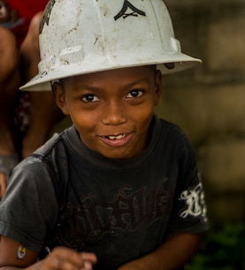 A young boy wears a hard hat while U.S. Marines with Special Purpose Marine Air-Ground Task Force-Southern Command continue construction on a new classroom at Victor Hugo School in Puerto Lempira, Honduras, Sept. 24, 2015. SPMAGTF-SC is a temporary deployment of Marines and Sailors throughout Honduras, El Salvador, Guatemala, and Belize with a focus on building and maintaining partnership capacity with each country through shared values, challenges, and responsibility. (U.S. Marine Corps Photo by Cpl. Katelyn Hunter/Released).