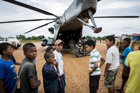Local children watch as U.S. Marines with Special Purpose Marine Air-Ground Task Force-Southern Command load gear into a CH-53 Super Stallion in Puerto Lempira, Honduras, Oct. 16, 2015. SPMAGTF-SC is a temporary deployment of Marines and Sailors throughout Honduras, El Salvador, Guatemala, and Belize with a focus on building and maintaining partnership capacity with each country through shared values, challenges, and responsibility. (U.S. Marine Corps Photo by Cpl. Katelyn Hunter/Released)