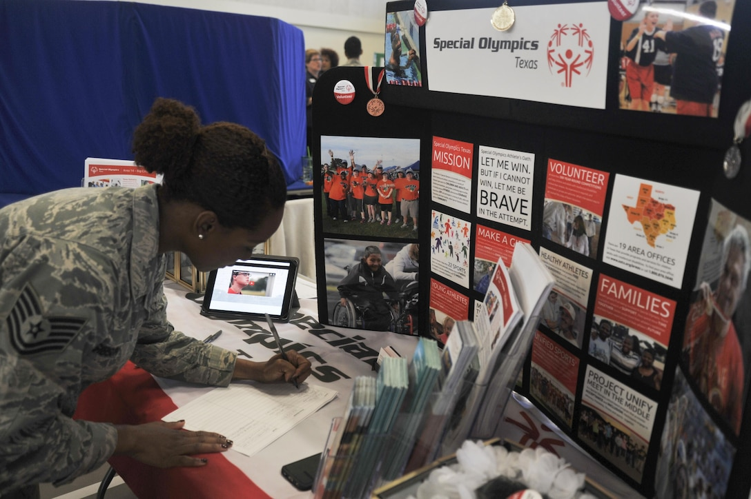 U.S. Air Force Tech. Sgt. Curtrell L. Gibson, 17th Force Support Squadron Airman Leadership School instructor, signs her name on a volunteer sheet at the Special Olympics booth during the Volunteer Fair at the Carswell Field House on Goodfellow Air Force Base, Texas, Oct. 28, 2015. Volunteers can serve as coaches, officials, committee members, competition assistants and more. (U.S. Air Force photo by Airman Chase Sousa/Released)