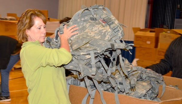 Lisa Grenon, of the Department of Veterans Affairs and the Veteran's Affairs Medical Center in Battle Creek, Michigan organizes backpacks from DLA Disposition Services for the annual Veterans Stand-down event.