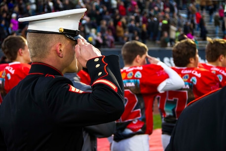 Sgt. Matthew Boulis, recruiter with Recruiting Sub Station Grand Rapids North, Mich., and a football player from Lowell High School, salute the flag during the National Anthem  before the start of the Great American Rivalry Series game between Lowell and East Grand Rapids high schools, Oct. 16, 2015. The Great American Rivalry Series games allowed Marines, football players and the school's student body to interact over a relatable common ground topic: competition.