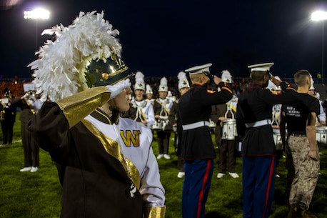 A Drum Major from Bay City Western High School, Staff Sgt. Luke DeJong and Sgt. Christopher Parker from Recruiting Sub Station Saginaw, Mich., salute the flag during the National Anthem before the start of the Great American Rivalry Series game between Bay City Central and Bay City Western high schools, Oct. 23, 2015. The Great American Rivalry Series games allowed Marines, football players and the school's student body to interact over a relatable common ground topic: competition.