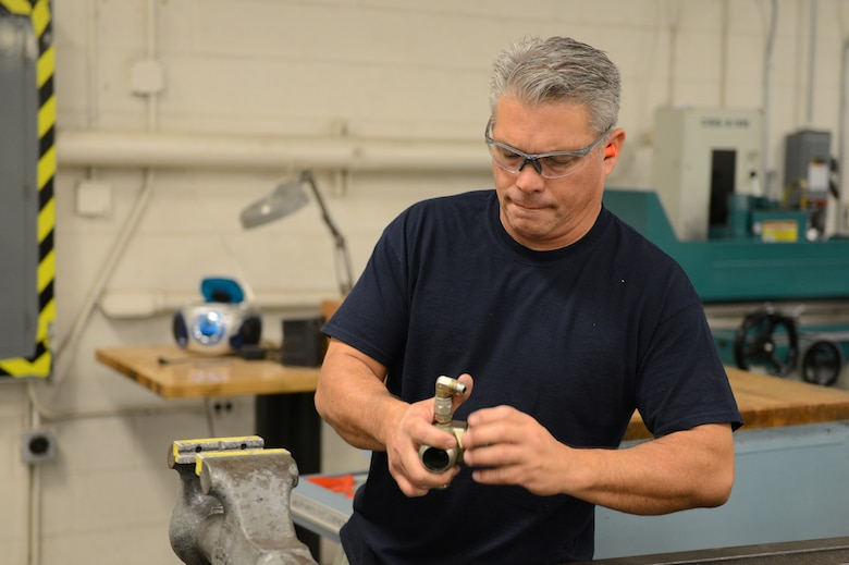 Craig Trujillo, 56th Equipment Maintenance Squadron civilian machinist, modifies a hydraulic test stand part at Luke Air Force Base, Arizona, Oct. 30, 2015. The part is for a Singaporean hydraulic test stand which needed to be converted from metric to U.S. customary. (U.S. Air Force photo by Senior Airman James Hensley)