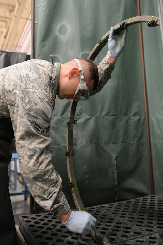 Airman 1st Class Bernard Moskalis, 56th Equipment Maintenance Squadron nondestructive inspection technician, performs a florescent penetrant inspection on an F-16 Fighting Falcon engine sink ring at Luke Air Force Base, Arizona, Oct. 30, 2015. (U.S. Air Force photo by Senior Airman James Hensley)