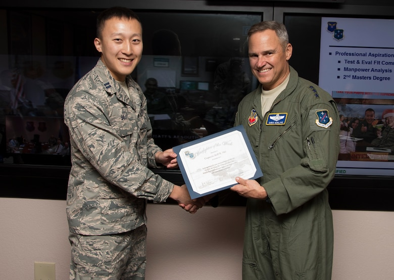 Capt. Jeff Shi, 12th Air Force (Air Forces Southern) operations research analyst, smiles after being presented the Warfighter of the Week from Lt. Gen. Chris Nowland, 12 AF (AFSOUTH) commander, during a staff meeting at Davis-Monthan AFB, Ariz., Oct. 19, 2015. War Fighter of the Week is an opportunity for the Airmen who represent 12th Air Force (Air Forces Southern) to share their own story. The Warfighter of the Week initiative aligns with the 12th Air Force (Air Forces Southern) commander's priority of creating a work environment where someone knows you both professionally and personally. (U.S. Air Force photo by Staff Sgt. Adam Grant/Released)