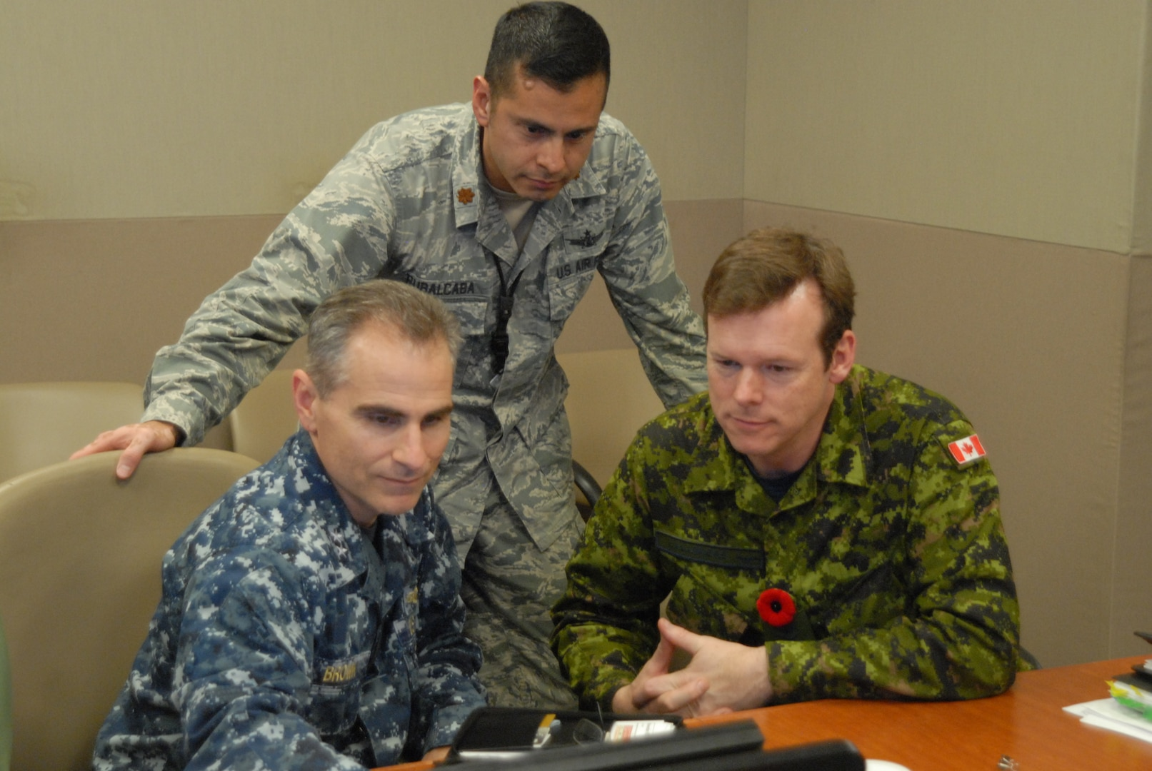 U.S. Navy Rear Adm. Brian Brown (seated left), Joint Functional Component Command for Space (JFCC Space) deputy commander, Royal Canadian Air Force (RCAF) Brig. Gen. Michel Lalumiere (seated right), RCAF Director General Space, and U.S. Air Force Maj. Daniel Rubalcaba, Rear Adm. Brown's executive officer, prepare for a battle update and assessment briefing, Nov. 3, 2015, at the Joint Space Operations Center, Vandenberg Air Force Base, Calif., in support of Exercise GLOBAL THUNDER 16. Allied participation in the exercise strengthens relationships with our international partners and provides additional levels of resiliency in our combined forces. GLOBAL THUNDER is an annual U.S. Strategic Command training event that assesses command and control functionality in all USSTRATCOM mission areas and affords component commands a venue to evaluate their joint operational readiness. Planning for GLOBAL THUNDER 16 has been under way for more than a year and is based on a notional scenario with fictitious adversaries. One of nine DoD unified combatant commands, USSTRATCOM has global strategic missions, assigned through the Unified Command Plan, which include strategic deterrence; space operations; cyberspace operations; joint electronic warfare; global strike; missile defense; intelligence, surveillance and reconnaissance; combating weapons of mass destruction; and analysis and targeting. (U.S. Air Force photo by Capt. Nicholas Mercurio/Released)