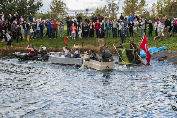 With dozens of spectators looking on and hurling water balloons in their direction, DLA Land and Maritime teams from the (l-r) Air Force, Navy, Army and Marine Corps take off during the first heat of the inaugural Navy Birthday Cardboard Regatta at the Eagle Eye Golf Course Oct. 16. The Navy team overcame a slow start to win the first heat and ultimately lost in the finals to a civilian team from Business Process Support.