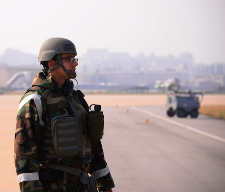 Staff Sgt. David Morales, a 51st Operations Support Squadron airfield management operations supervisor, watches a jet land on flightline Nov. 3, 2015, at Osan Air Base, South Korea. Morales and more than 16,000 other personnel are participating in readiness exercise Vigilant Ace 16, a large-scale exercise designed to test the combat capabilities and enhance the interoperability of the U.S. and South Korean air forces. (U.S. Air Force photo/Staff Sgt. Benjamin Sutton)