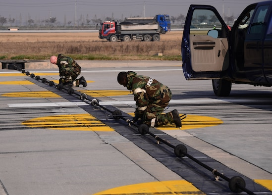 Airmen assigned to 51st Civil Engineer Squadron barrier management flight raise a barrier cable in the event a fighter jet over shoots the runway or during an emergency Nov. 3, 2015, at Osan Air Base, Republic of Korea. Barrier management airmen and airfield managers from the 51st Fighter Wing ensure the flightline is operational for aircraft participating in readiness exercise Vigilant Ace 16. Vigilant Ace 16 is a large-scale exercise designed to test the combat capabilities and enhance the interoperability of the U.S. and Republic of Korea Air Forces. (U.S. Air Force photo/Staff Sgt. Benjamin Sutton)