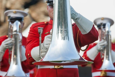 """U.S. Marines with the U.S. Marine Corps Drum and Bugle Corps perform during the evening parade at the Marine Corps War Memorial, Arlington, Va., May 26, 2015.Since September 1956, marching and musical units from Marine Barracks Washington, D.C., have been paying tribute to those whose """"uncommon valor was a common virtue"""" by presenting sunset parades in the shadow of the 32-foot high figures of the United States Marine Corps War Memorial. (U.S. Marine Corps photo by Lance Cpl. Alejandro Sierras/Released)"""