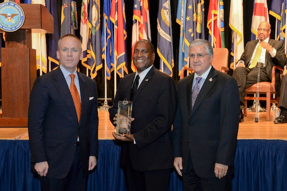 Brad Carson, the acting undersecretary of defense for personnel and readiness, presents the secretary of defense award for the best disability program among large military components to Bob Corsi, the assistant deputy chief of staff of manpower, personnel and services, and Dr. Jarris Taylor, deputy assistant secretary of strategic diversity integration, during a ceremony at the Pentagon Oct. 29, 2015. For the past 35 years, the Office of Diversity Management and Equal Opportunity has recognized outstanding service members and Defense Department civilian personnel with disabilities at an annual awards ceremony. (U.S. Army photo/Sgt. Courtney Russell)