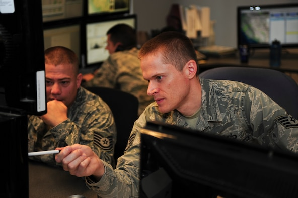 U.S. Air Force Staff Sgt. John Grotans, 25th Operational Weather Squadron zone shift supervisor, conducts on-the-job training with Tech. Sgt. Matthew Ordorff, 25th OWS shift supervisor, at Davis-Monthan Air Force Base, Ariz., Oct. 29, 2015. Shift supervisors are in charge of a section that forecasts weather for specific regions of the U. S. (U.S. Air Force photo by Airman Basic Nathan H. Barbour/Released)