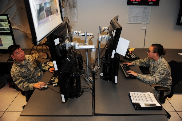 U.S. Air Force Senior Airmen James Kim and Airman 1st Class Ariel Hawkins, 25th Operational Weather Squadron weather forecasters, monitor weather conditions at Davis-Monthan Air Force Base, Ariz., Oct. 29, 2015. The 25th OWS operations floor is divided into north, south and central sections, forecasting the weather for the Western part of the Continental U.S. (U.S. Air Force photo by Airman Basic Nathan H. Barbour/Released)