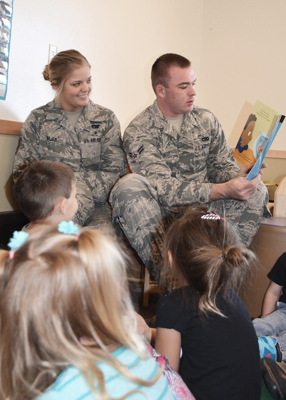 120th Airlift Wing Airmen Staff Sgt. Ashlee Wajer and Airman 1st Class Devon Kennedy volunteer to read a children's book to students in a daycare in Great Falls, Mont., Oct. 22, 2015. (U.S. Air National Guard photo by Senior Master Sgt. Eric Peterson/Released)