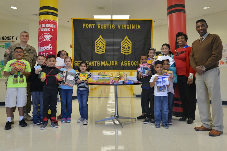 The Eustis Sergeants Major Association stands with General Stanford Elementary School students and faculty by a table of donated school supplies at Fort Eustis, Va., Oct. 30, 2015. Each year, the association teams up with the school to prioritize, collect and donate items that enable students to complete required school projects throughout the year. (U.S. Air Force photo by Staff Sgt. Natasha Stannard/Released)