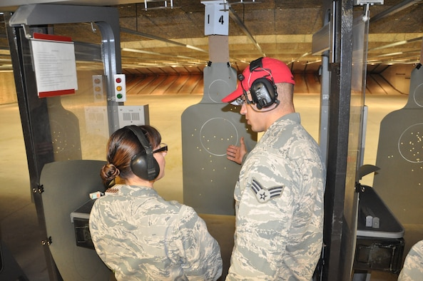 Senior Airman Daniel Conrad, 88th Security Forces Squadron CATM instructor, reviews an M9 qualifications course student's target with her. (U.S. Air Force photo/Bryan Ripple.)