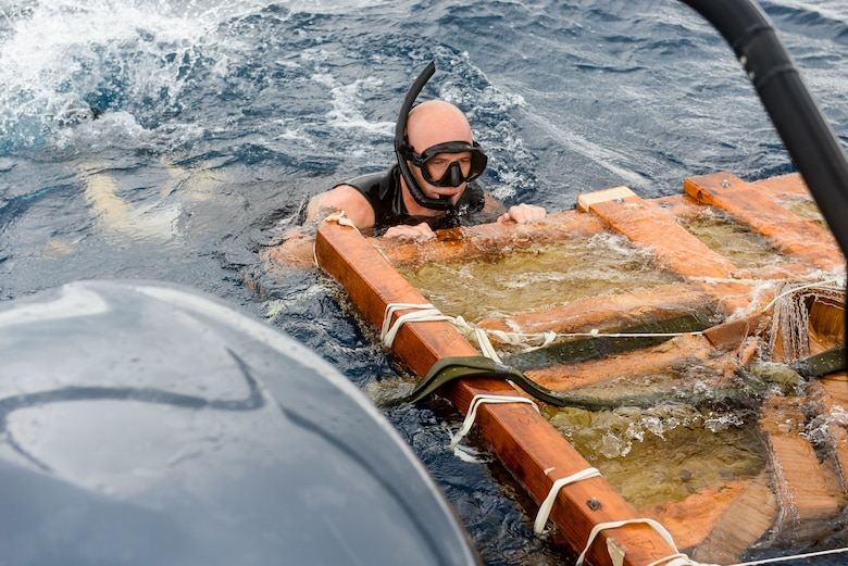 U.S. Air Force Staff Sgt. Jason Fischman, 31st Rescue Squadron pararescueman, recovers a platform that was used to airdrop a guardian angel rescue craft Oct. 31, 2015, near the coast of White Beach Naval Base, Japan. A boat party from the 31st RQS aided a long-range search and rescue exercise with members from Alaska Air National Guard's 212th RQS, who were airdropped after a flight from Joint Base Elmendorf-Richardson. (U.S. Air Force photo by Senior Airman John Linzmeier)