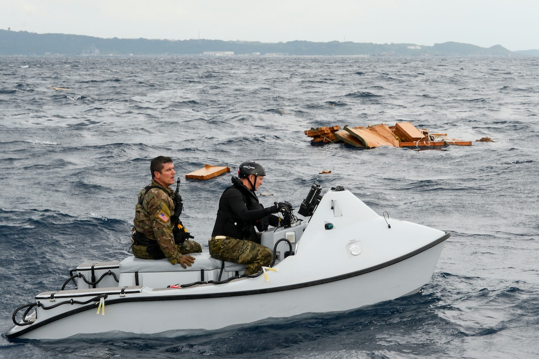 U.S. Air Force Master Sgt. Shane Hargis, Alaska Air National Guard's 212th Rescue Squadron pararescueman, and Maj. Jay Casello, 212th RQS combat rescue officer, begin a mock search for survivors aboard a Guardian Angel rescue craft Oct. 31, 2015, near the coast of White Beach Naval Base, Japan. The rescue team was airdropped by a C-17 Globemaster from Alaska ANG's 249th Airlift Squadron in a long range search and rescue exercise. (U.S. Air Force photo by Senior Airman John Linzmeier)