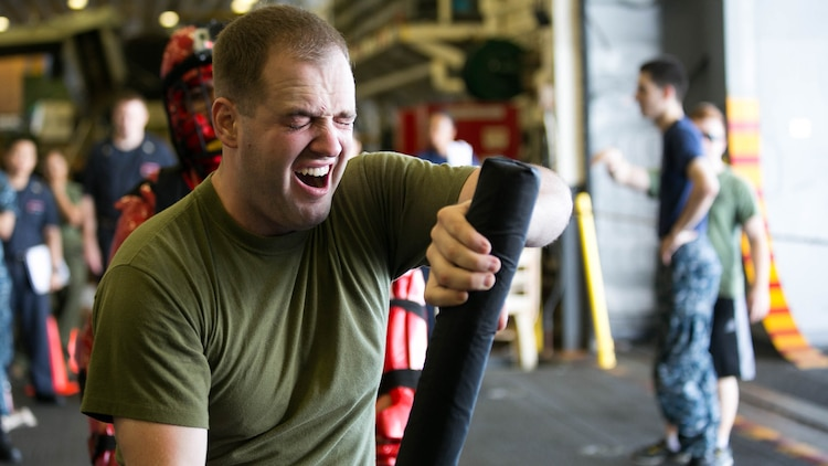 Sgt. Benjamin Stewart practices baton techniques after being sprayed with oleoresin capsicum aboard the USS Essex on the Indian Ocean, Oct. 31, 2015 during a non-lethal weapons course. Stewart is an intelligence specialist with Combat Logistics Battalion 15, 15th Marine Expeditionary Unit. U.S. Marines and Sailors were sprayed across the face with OC spray and went through a series of exercises as their final event of the course.